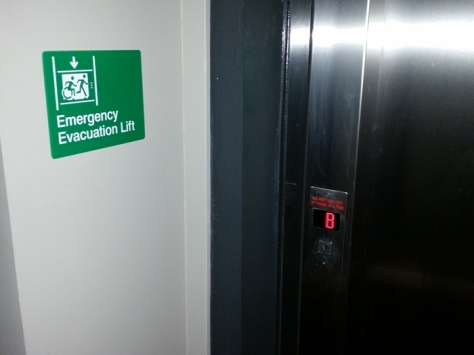 Braille Sign Supplies Emergency Evacuation Lift Sign on Wall, next to lift doors